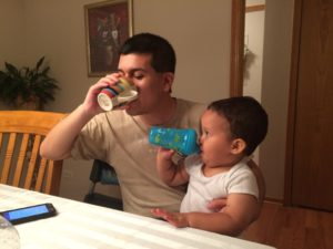 Alejandro and my almost 2-year-old brother, Jonathan. Jonathan is on his lap. He is holding his sippy-cup as he mimics Alejandro drinking from his cup.