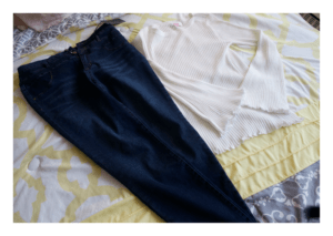 Bell sleeved top and high waisted jeans laid out on my bed.