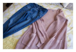 Pink cardigan and jeans laid out on my bed.