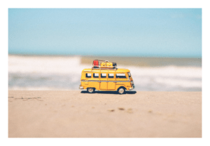 A tiny yellow camper toy on the beach.