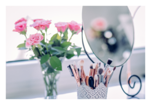 Pink roses in a vase, a makeup brush holder, brushes, and vanity mirror.