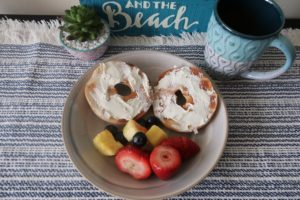 Plated plain bagels and cream cheese, strawberries, blueberries, and chopped pineapple, and a mug of water.
