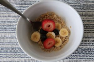 A bowl of oatmeal with strawberries, blueberries, and chopped banana.