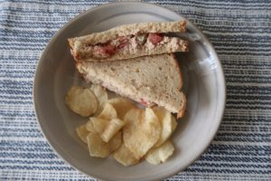 Plated tuna salad sandwich and Lay's kettle cooked sea salt and vinegar potato chips.