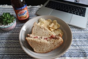 Plated tuna sandwich, kettle cooked potato chips, and Snapple peach tea.