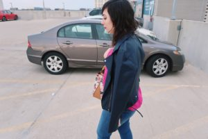 I'm walking in the parking lot of The Fashion Outlets of Chicago, wearing my leather jacket.