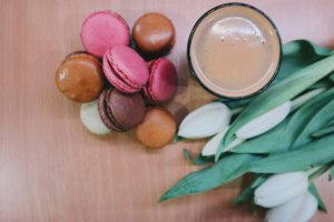 Macaroons, a cup of coffee, and white tulips.