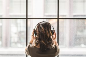 A woman listening to music with headphones on.