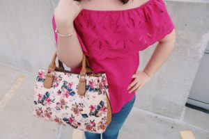 Close up shot of my off-the-shoulder top and floral purse.