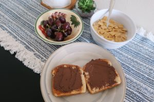 Toast with nutella, grapes, and Quaker Oats Life cereal.