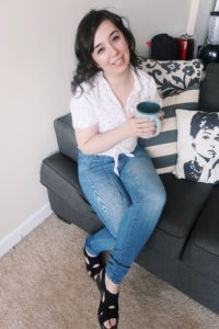 I'm enjoying a cup of coffee, wearing a white polka dot blouse, jeans, and black sandals.