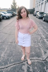 I'm wearing a pink top, white mini skirt, and white sandals.