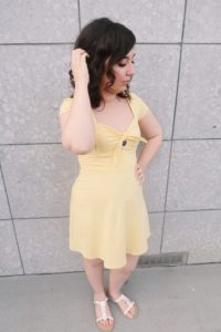 I'm wearing a casual yellow sundress and white sandals.