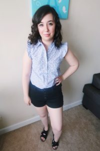 I'm wearing a blue floral blouse, black shorts, and black sandals.