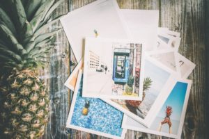 Pineapple and photographs laid out in front of a wooden background.