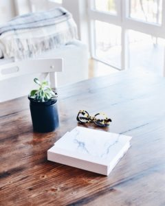 Glasses, book and plant on table.