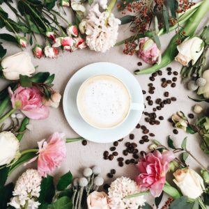 Flowers, coffee beans, and cup of coffee.