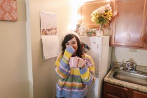 Wearing colorful striped sweater and pink knit beanie.