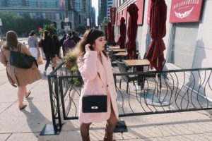 Wearing pink overcoat and business outfit.