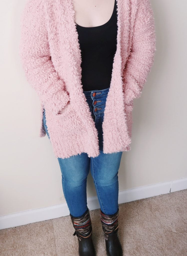 Pink fuzzy cardigan and high waisted jeans.