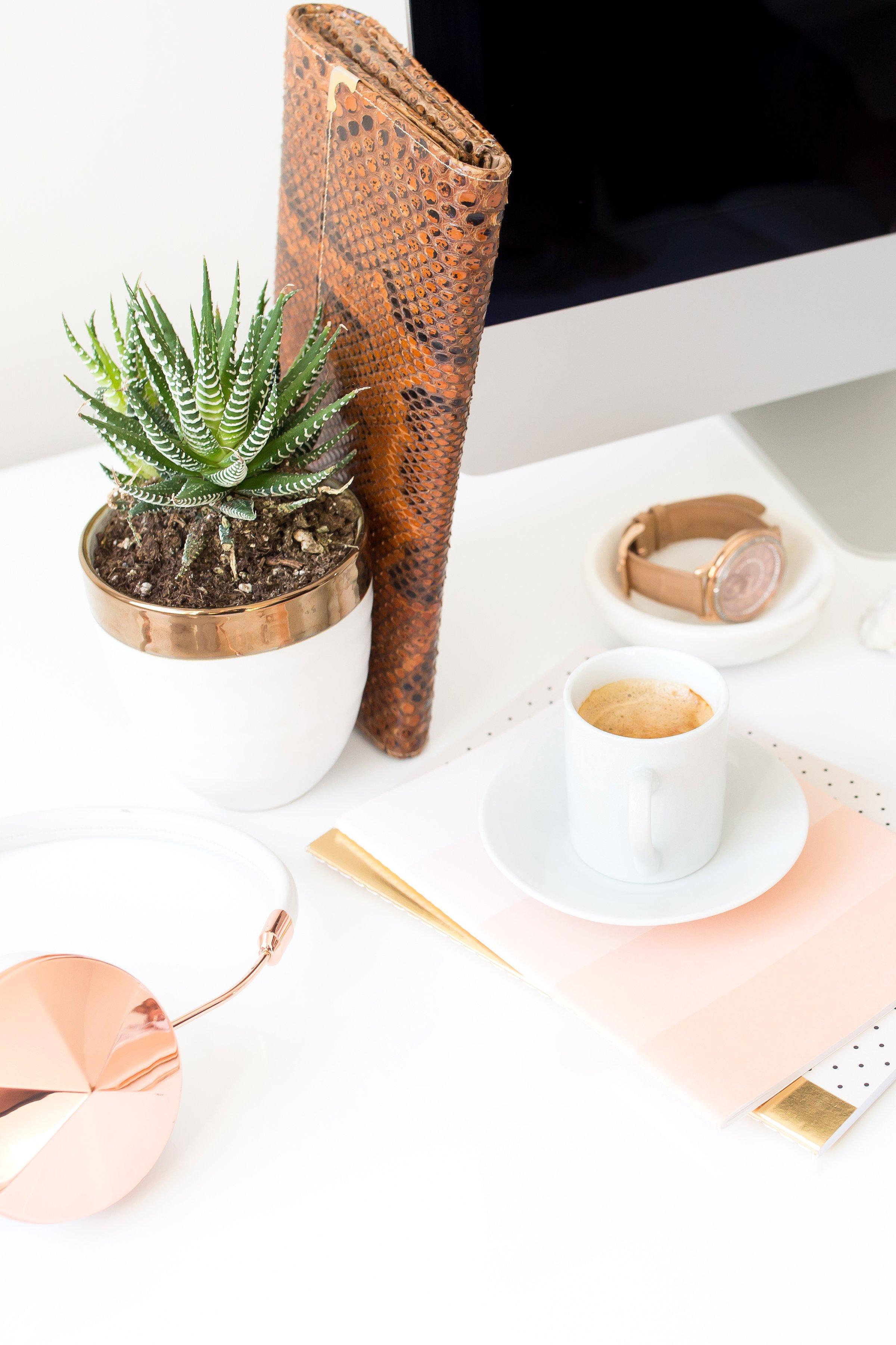 Freshly brewed espresso sitting on a peach styled desk.