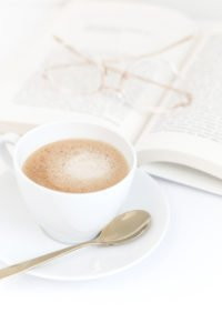 An open book, reading glasses, and cup of coffee.