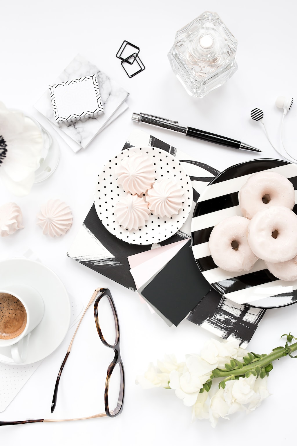 Coffee, flowers, donuts, and perfume flatlay.