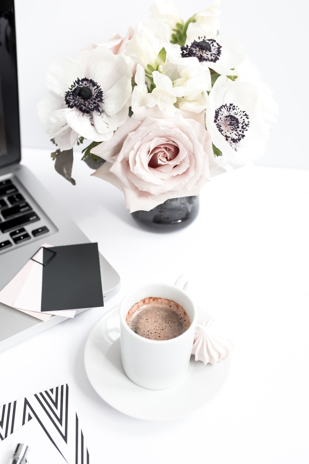 Flowers and coffee on a desk.