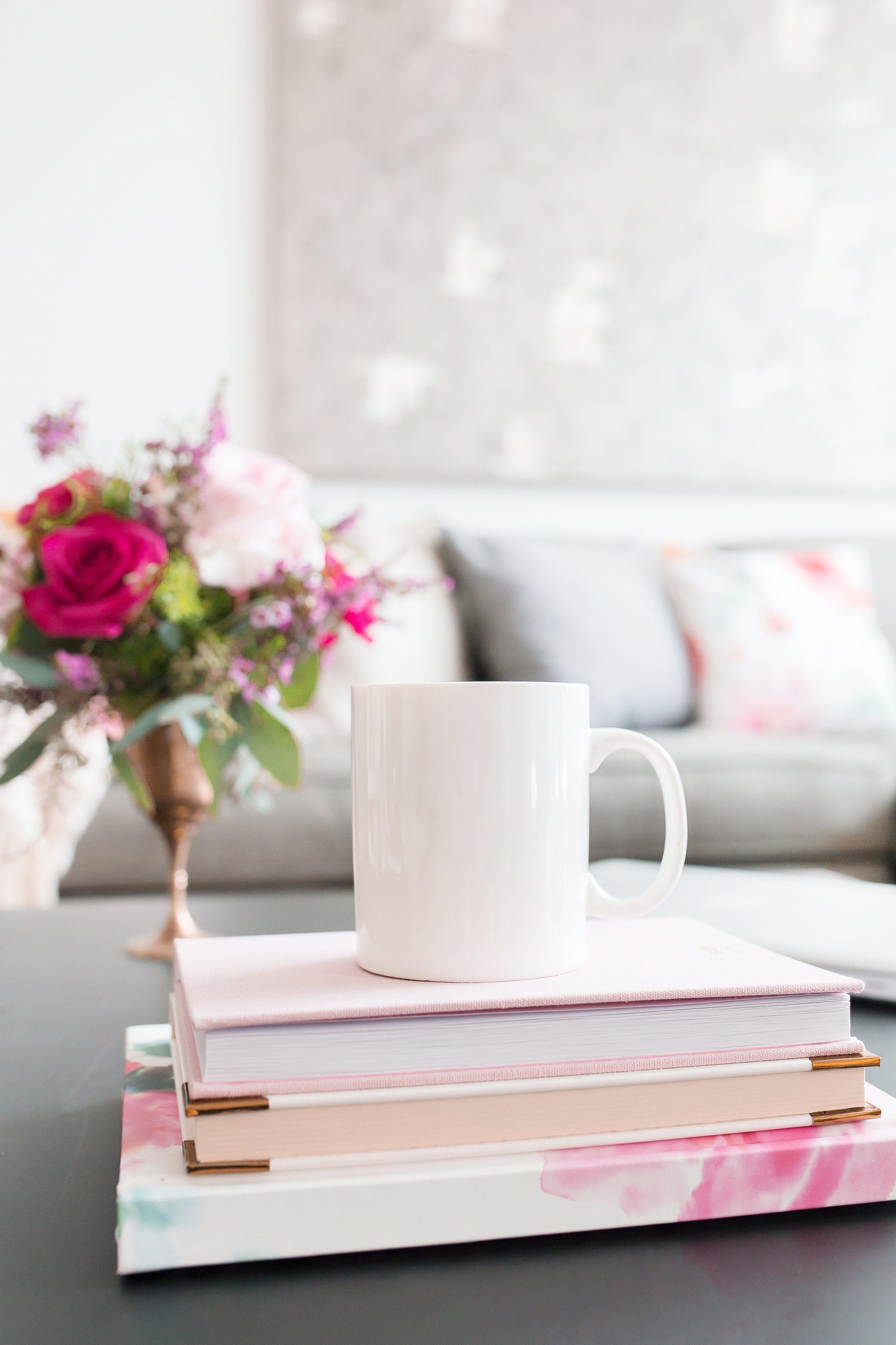 Flowers, books and mug on a coffee table.
