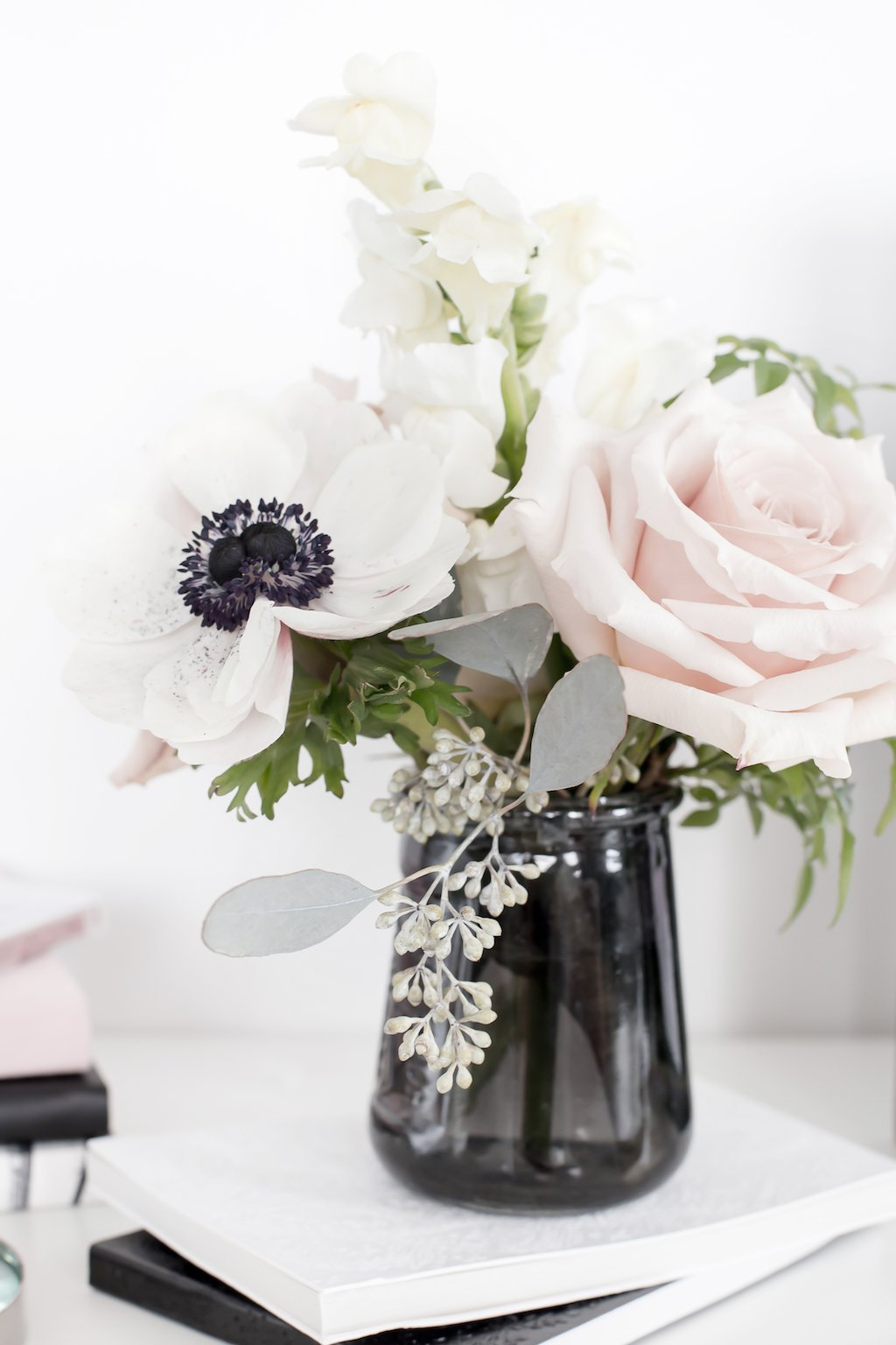 Vase with pink, black, and white flowers.