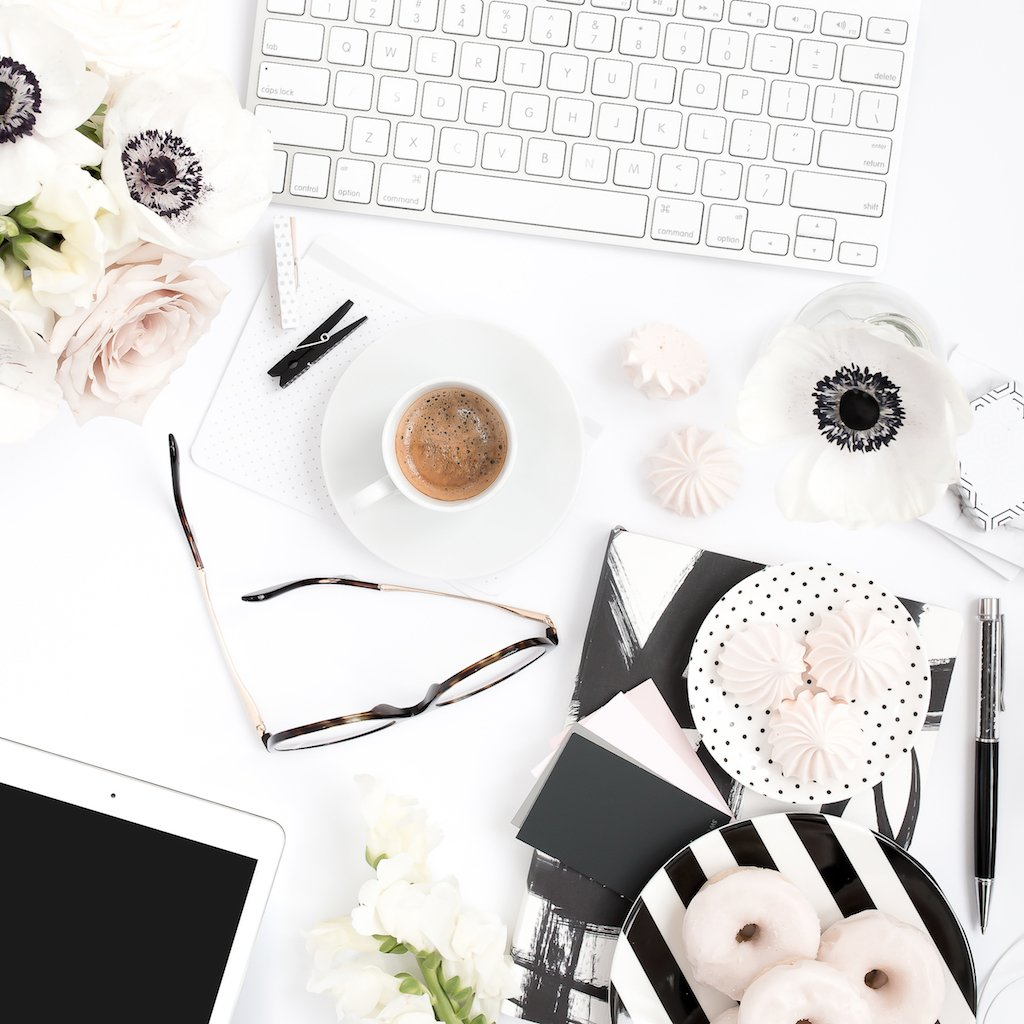 A keyboard on a blush and black styled desktop with coffee and sweets.
