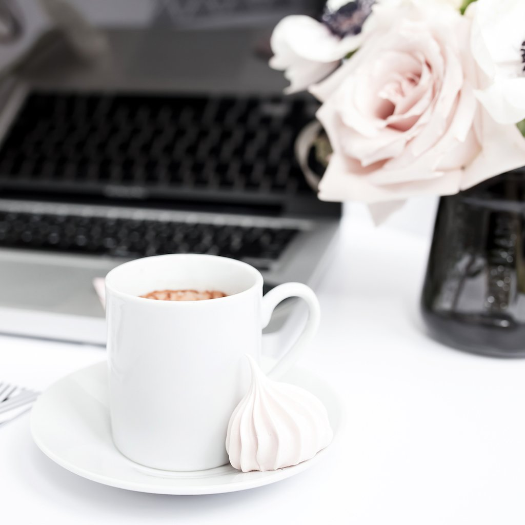 A cup of coffee, a laptop and a beautiful blush rose on a white desk.