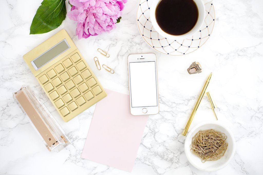 A marble desktop featuring an iPhone mockup, a paper mockup, a golden calculator and a coffee.