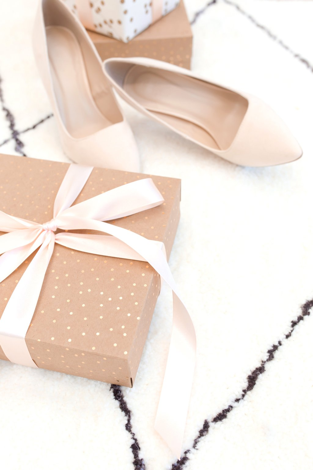 Pretty wrapped present on carpet next to blush high heels.
