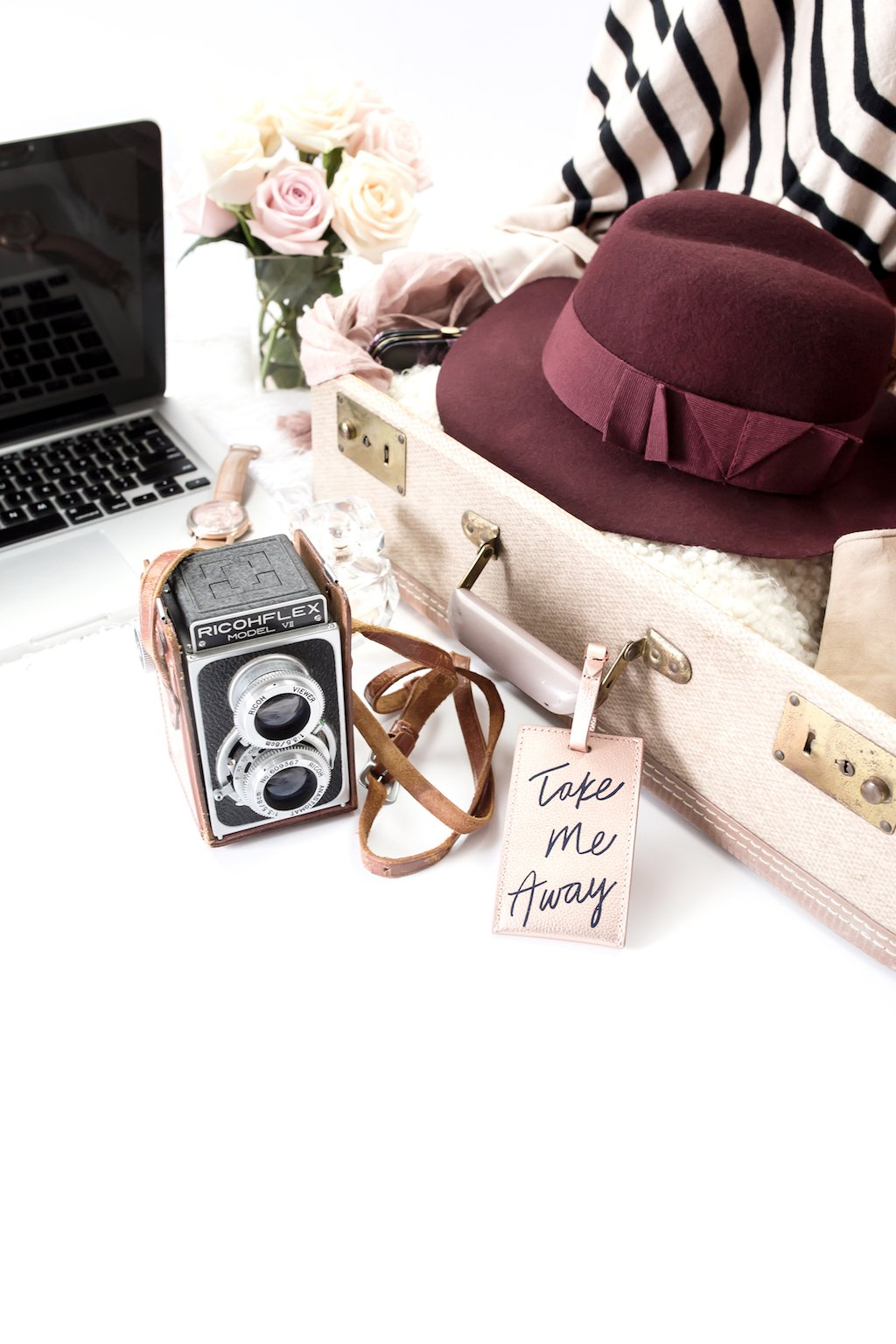 An open suitcase with clothing, hat, a laptop and a camera