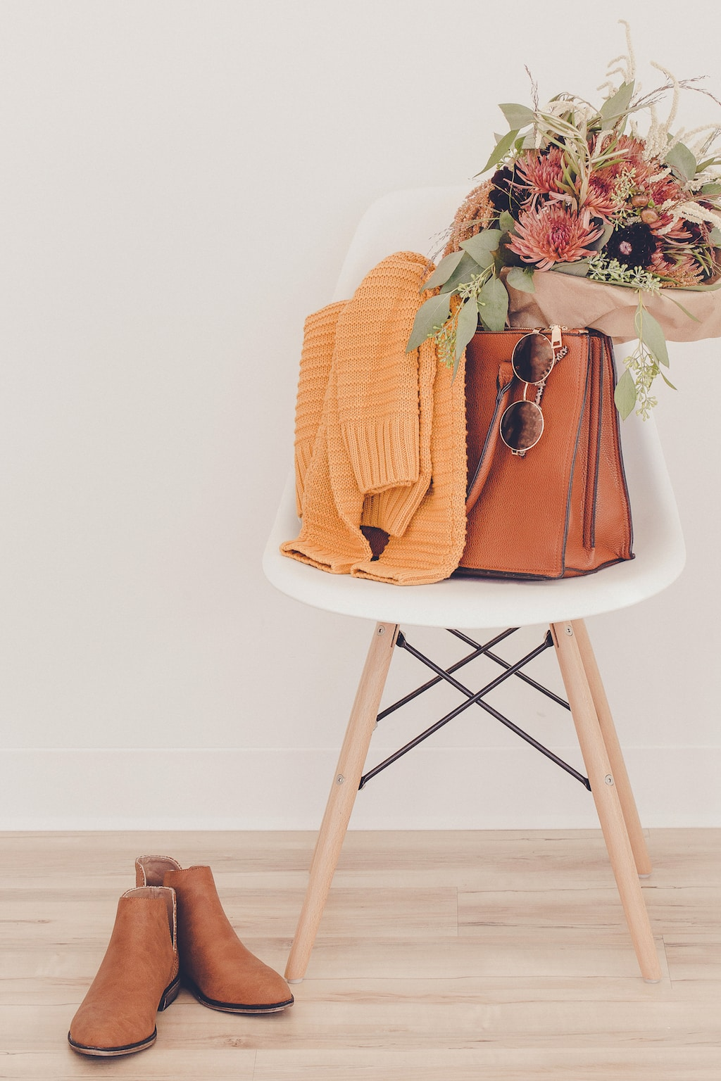 Purse on chair with flowers and cozy sweater.